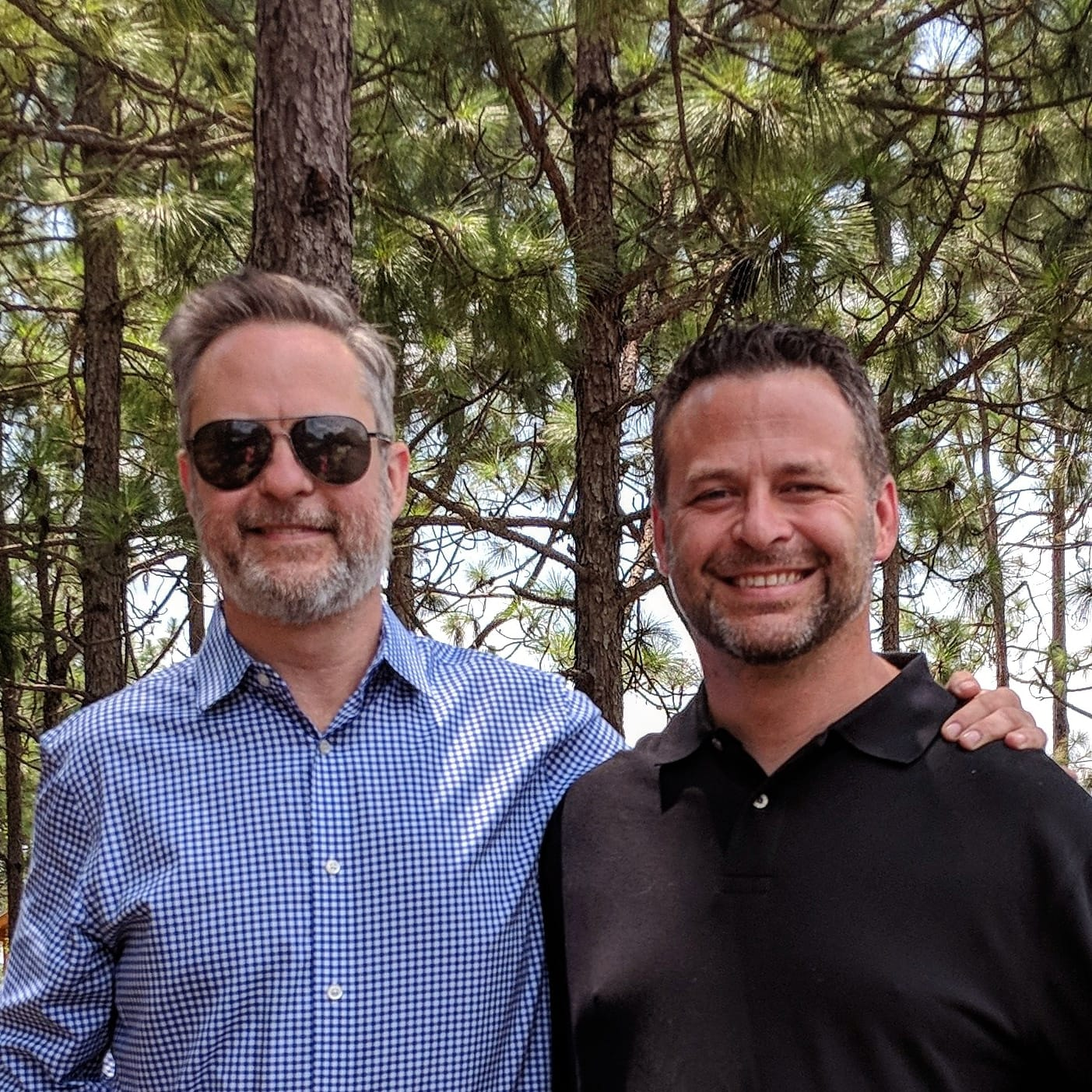 A picture of two brothers standing near pine trees in Georgia
